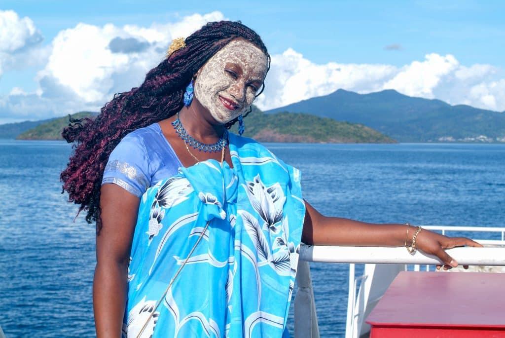 femme sur la barge à Mayotte portant le masque de bois de santal